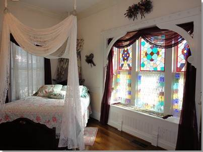 Queen-sized bed next to the original 1884 stained glass window